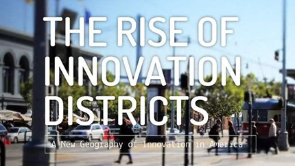 "Cover of the report ""The Rise of Innovation Districts"": text over blurry urban streetscape."