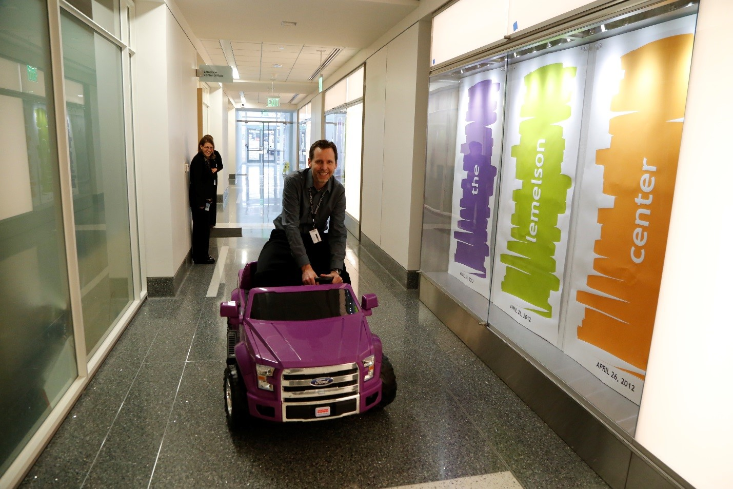 """Outside the Lemelson Center offices, Tim test-drives a toy ride-on car he modified for Spark!Lab's 'Adaptive Driving' activity during 'Things That Roll.'"""""""
