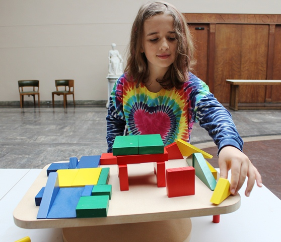 A young girl experiments with the teeter table and blocks at Spark!Lab at the Berkshire Museum.