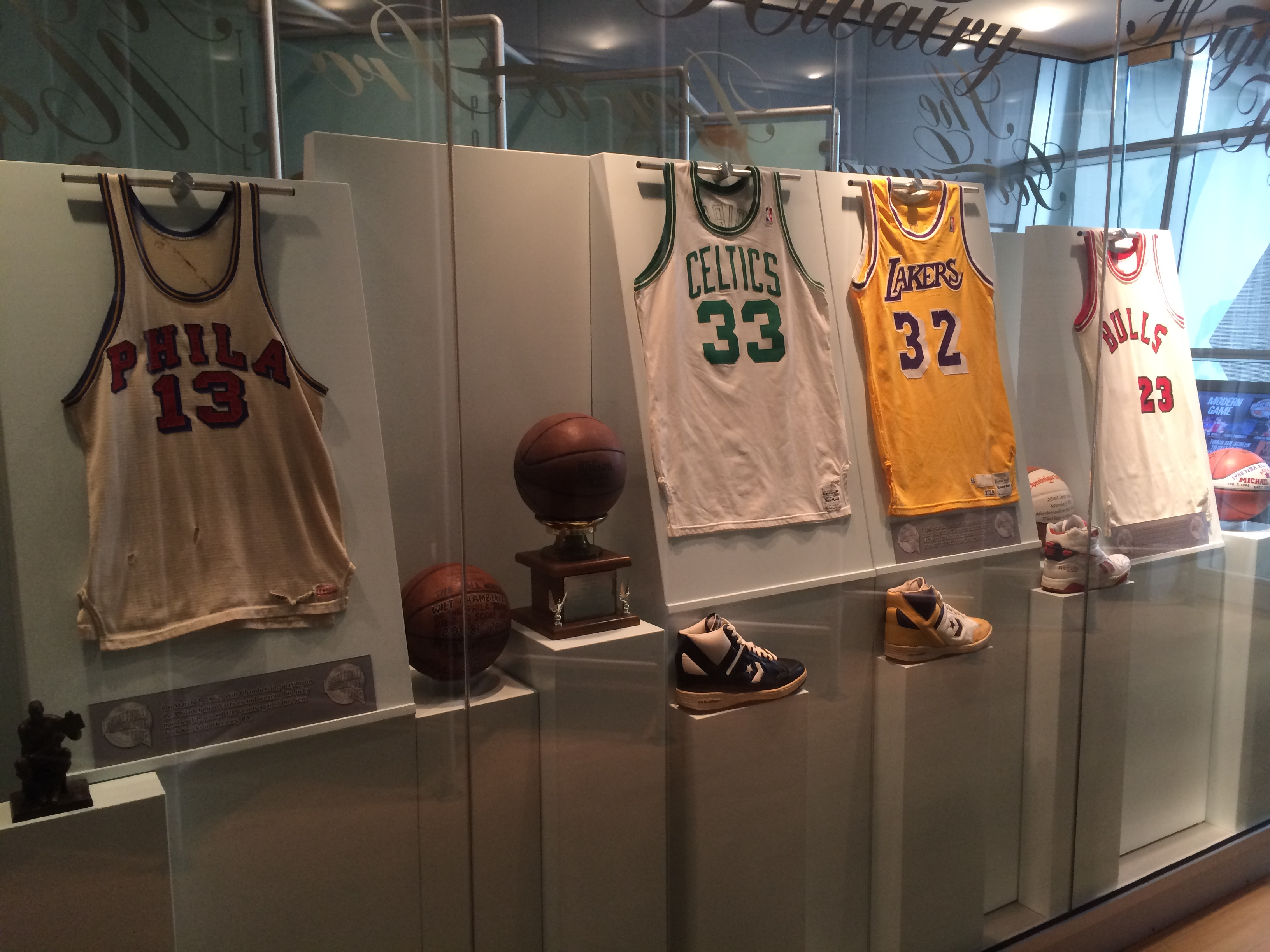 """Left to right, jerseys and shoes from Hall of Famer, Wilt Chamberlain (#13), Larry Bird (#33), Ervin """"Magic"""" Johnson (#32) and Michael Jordan (#23), at the Naismith Memorial Basketball Hall of Fame in Springfield, MA."""