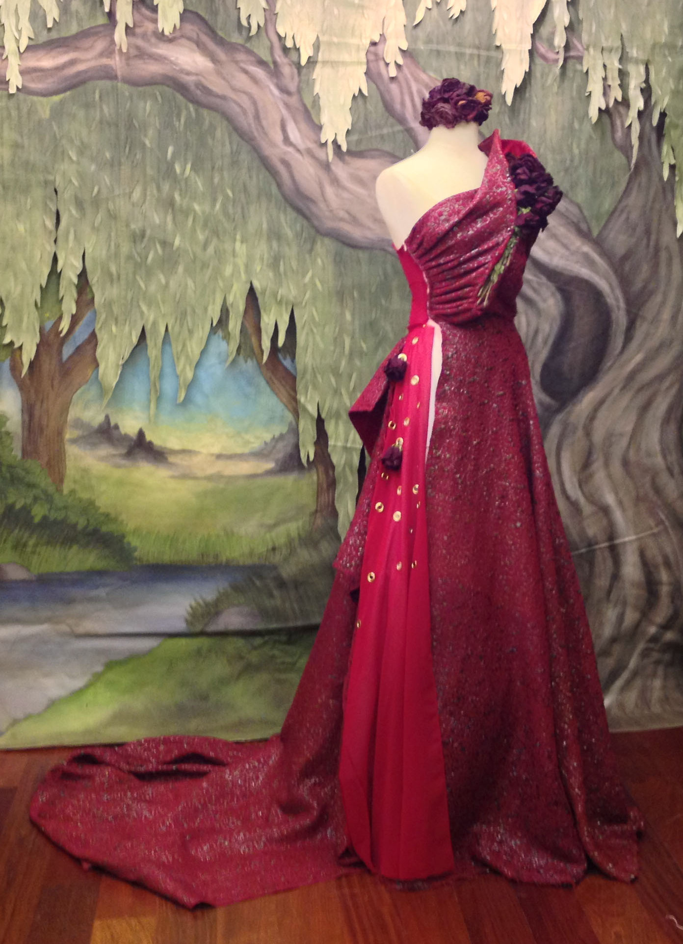 "The ""Alexis Rose"" holiday dress made of gospel and holiday-themed audio cassette tapes, red velvet from a Mrs. Claus costume, wire hangers, and donated grommets filled with roses. Sue Lawton's ""Willow Tree"" is in the background."