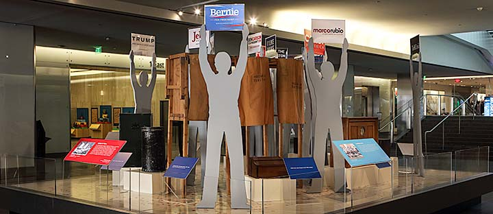 A display of historical voting apparatus and modern campaign posters at the National Museum of American History