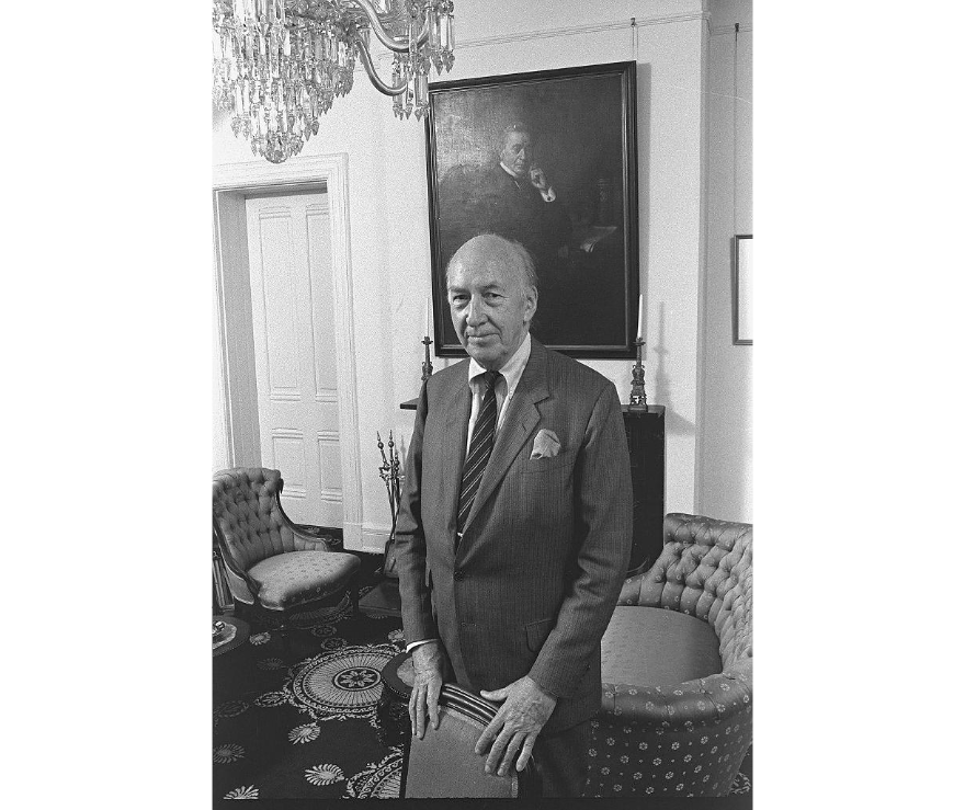 S. Dillon Ripley, eighth Smithsonian Secretary (1964-1984), standing in the Secretary's Parlor in the Smithsonian Institution Building in front of the portrait of Joseph Henry, first Secretary of the Smithsonian