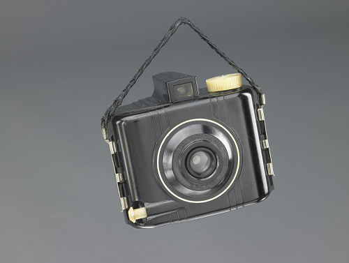 Popular from the 1939 World's Fair into the 1950s, the Kodak Baby Brownie Special was a small black camera made of bakelite, with white shutter button and winding knob and featuring a braided strap.