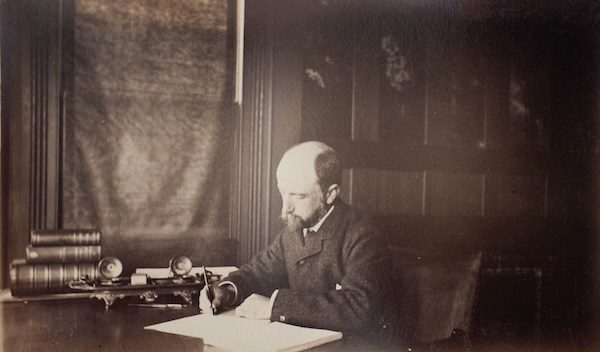 Henry Adams seated at his desk, 1883