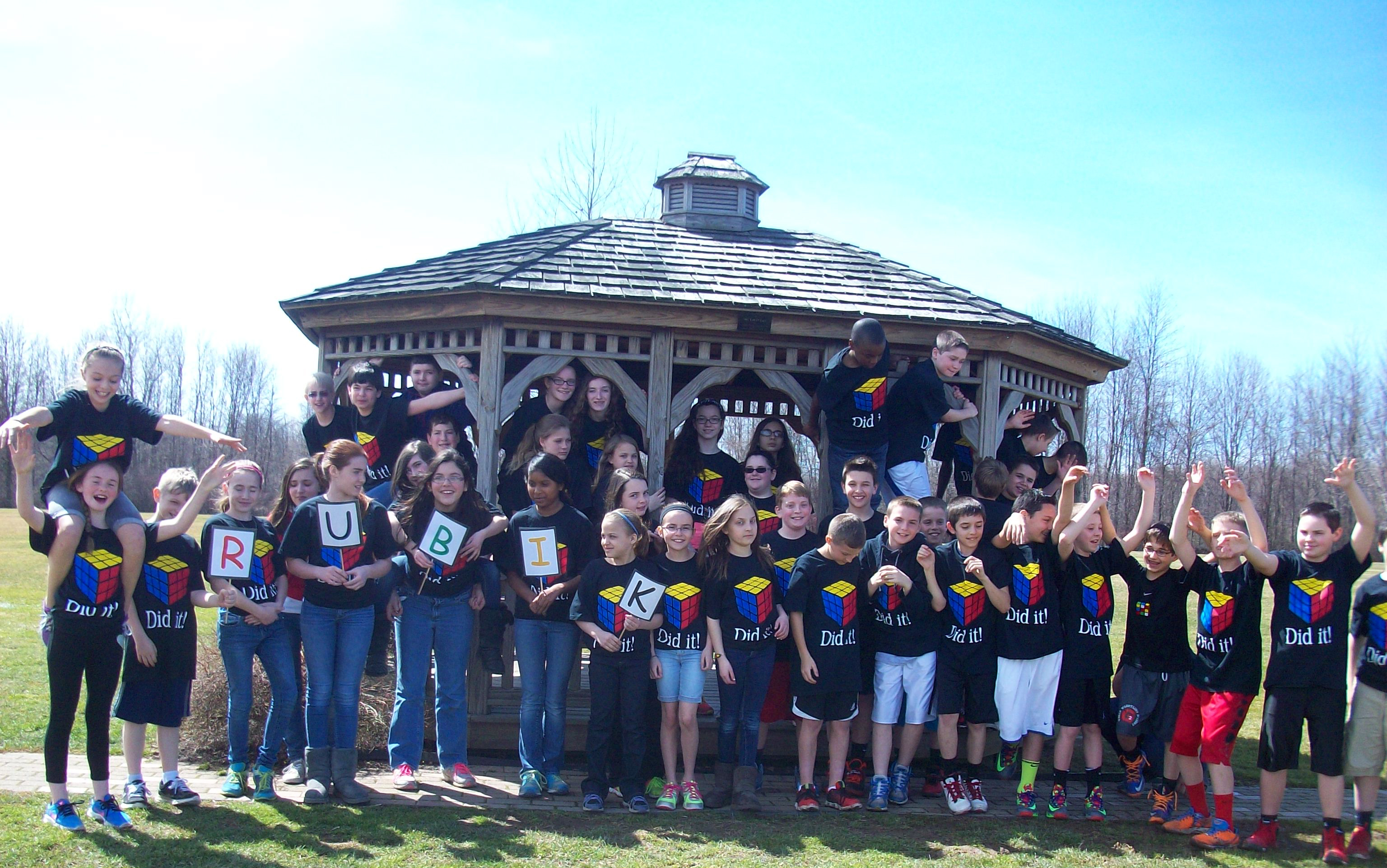 Large group of elementary school aged children wearing black t-shirts with the Rubik's cube in the center.