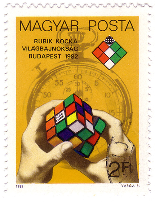 Hungarian stamp honoring the Rubik's cube: hands manipulating Rubik's cube with stopwatch in background. Via Wikimedia Commons.