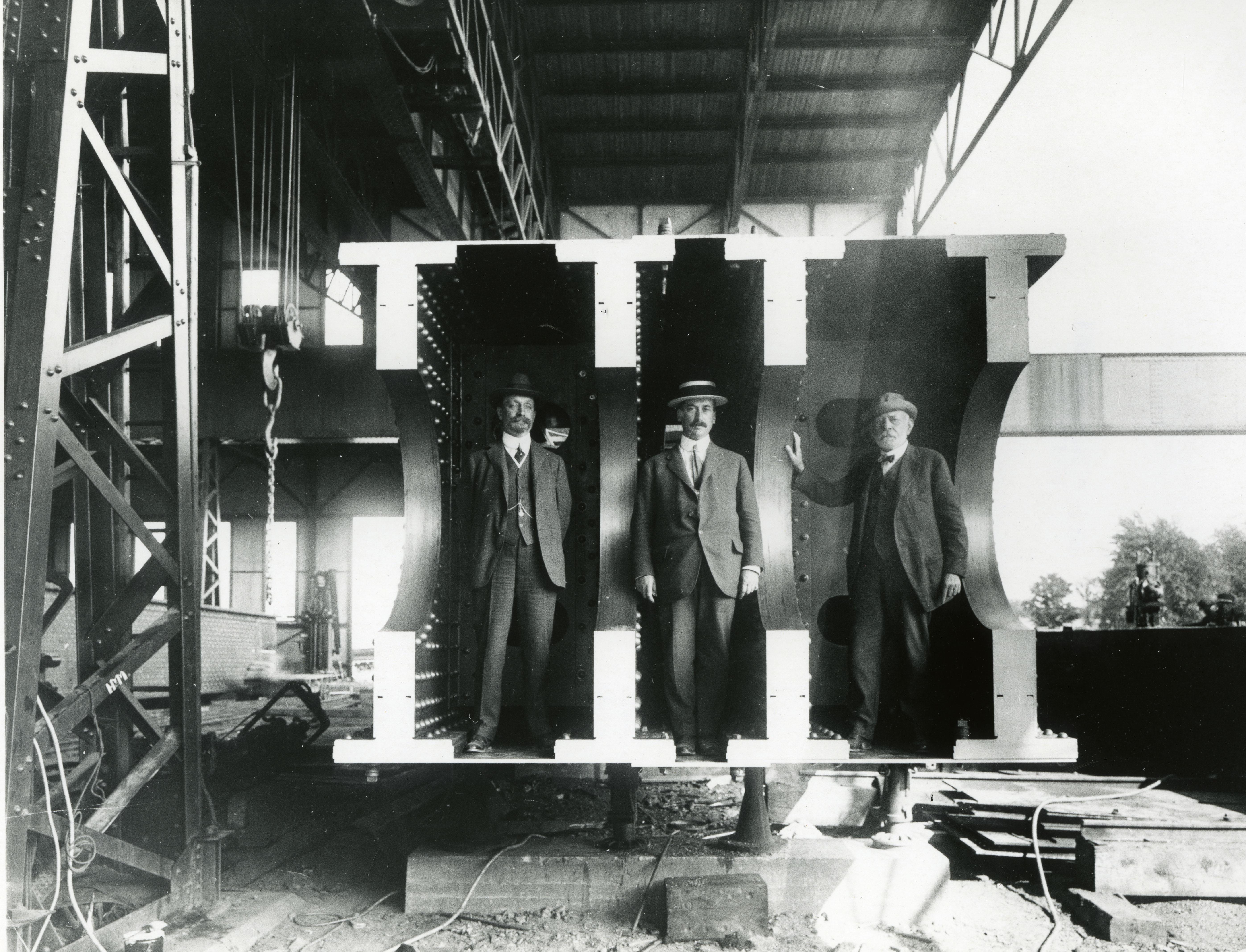 Photograph of Quebec Bridge Board of Engineers standing in bridge cantilever, left to right: Ralph Modjeski, Charles Monsarrat and C.C. Schneider, circa 1910s.