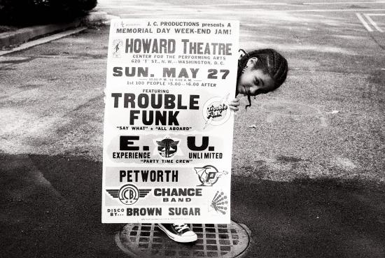 A child holds a billboard for Memorial Day shows at the Howard Theatre, featuring Trouble Funk and Experience Unlimited. Photograph by Thomas Sayers Ellis, used with permission.