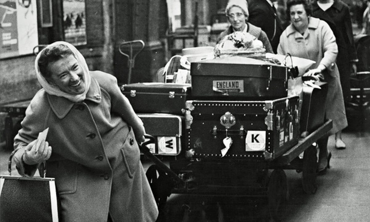 English women with luggage on cart, undated, via The Guardian.