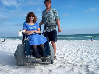 nventor Michael Deming with his wife Karen on a beach. Karen sits in a wheelchair with all-terrain wheels, specifically invented by Deming to be used on the beach.