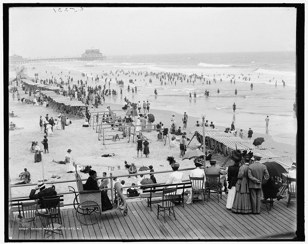Black and white photo of crowds on the beach in Atlantic City, NJ, 1908.