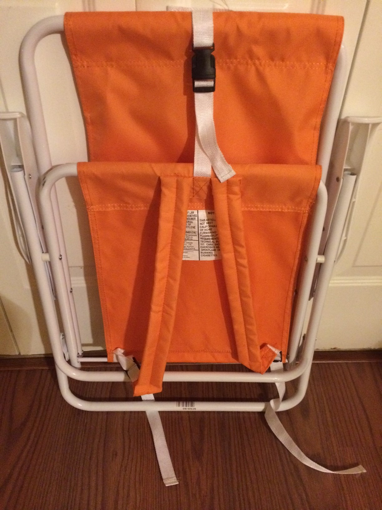 Orange and white beach chair that can be worn like a backpack.