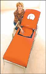"""Shannon Nation with her orange """"Pregnancy Beach Chair,"""" which has a hole so that pregnant women can lie comfortably on their stomachs."""