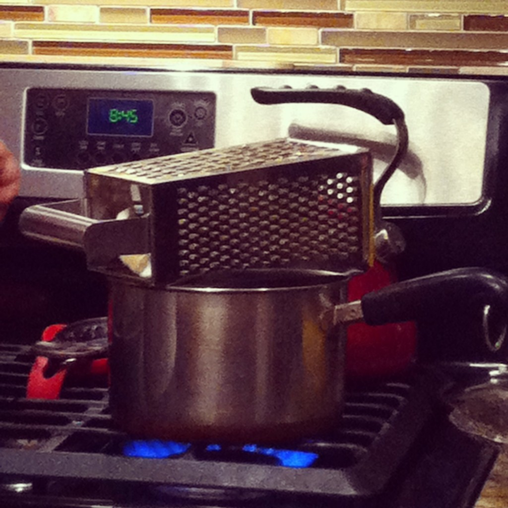 Cheese grater holding a head of cauliflower over a pot of water on the stove.