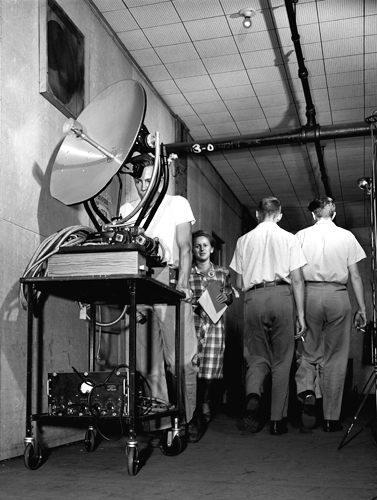 An employee pushes a microwave radar dish down a Rad Lab corridor.