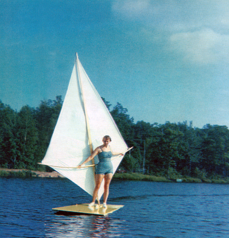 A woman rides a sailboard (or windsurfer) invented by Newman Darby