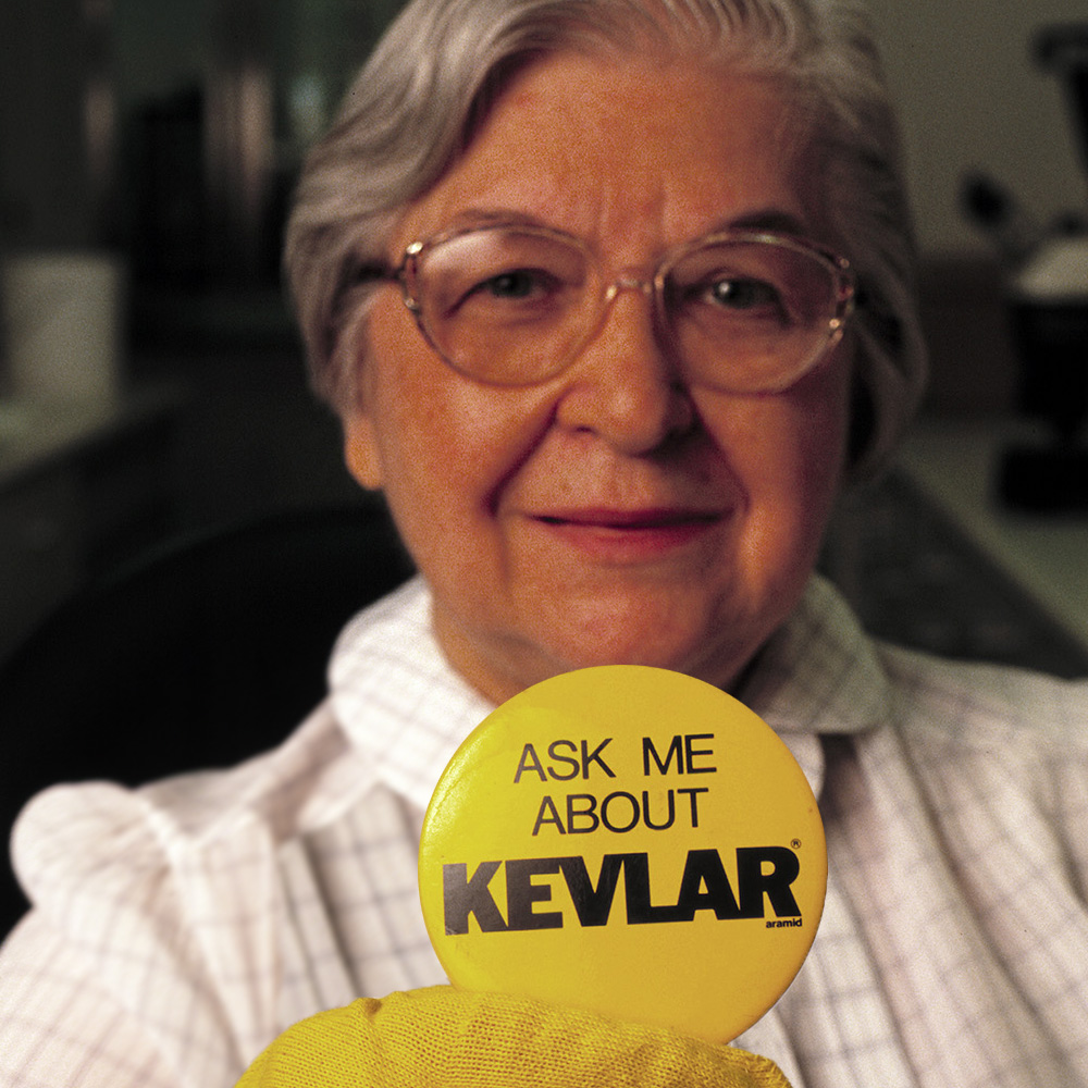 Stephanie Kwolek, approximately 70 years old, holding up a button that reads Ask Me About Kevlar.