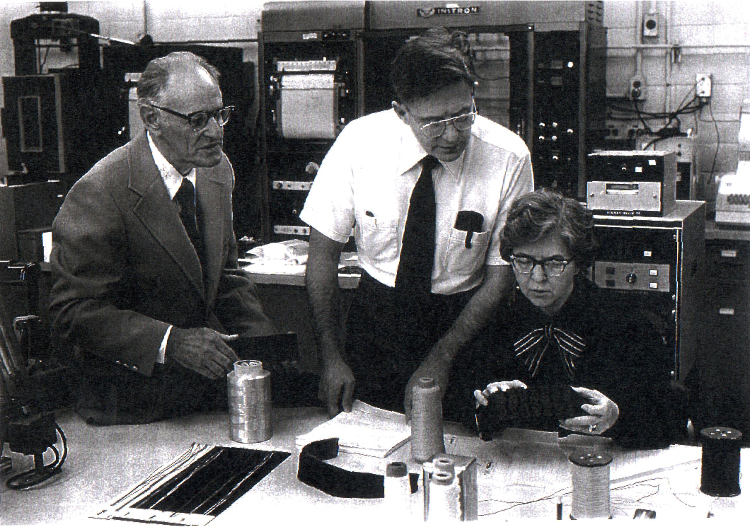 Dr. Paul Morgan, Dr. Herbert Blades, and Stephanie Kwolek are pictured in the DuPont Textile Fibers Pioneering Research Laboratory. Kwolek sits at a table holding a Kevlar sample while the men look on. 1960s-era computer equipment is in the background.