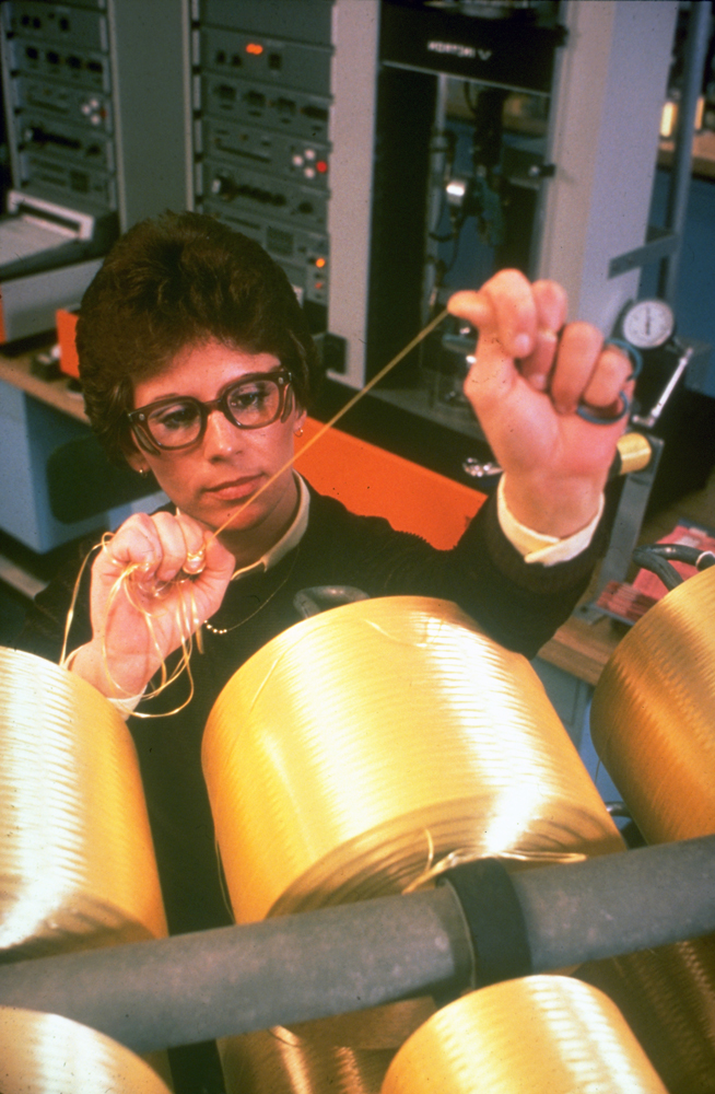 A woman draws a strand of Kevlar from one of several spools in front of her at a manufacturing site in Richmond, Virginia. 1970s-era computer equipment is in the background.