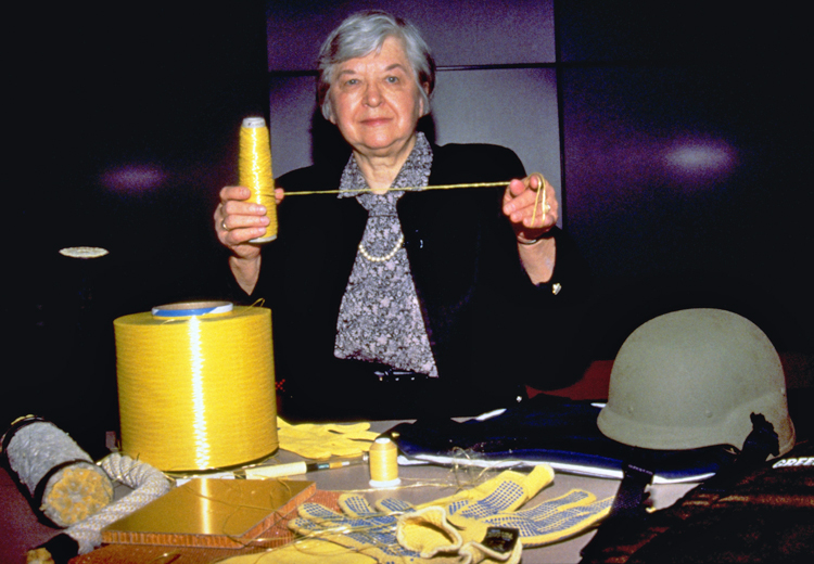 Stephanie Kwolek holds a spool of yellow Kevlar thread in her right hand and has pulled out a thread and stretched it about 16 inches with her left hand. She has short gray hair and is wearing a gray patterned shirt and pearl necklace under a black jacket. A larger spool of Kevlar fiber, a rope, gloves, and a helmet are displayed on a table in front of her.