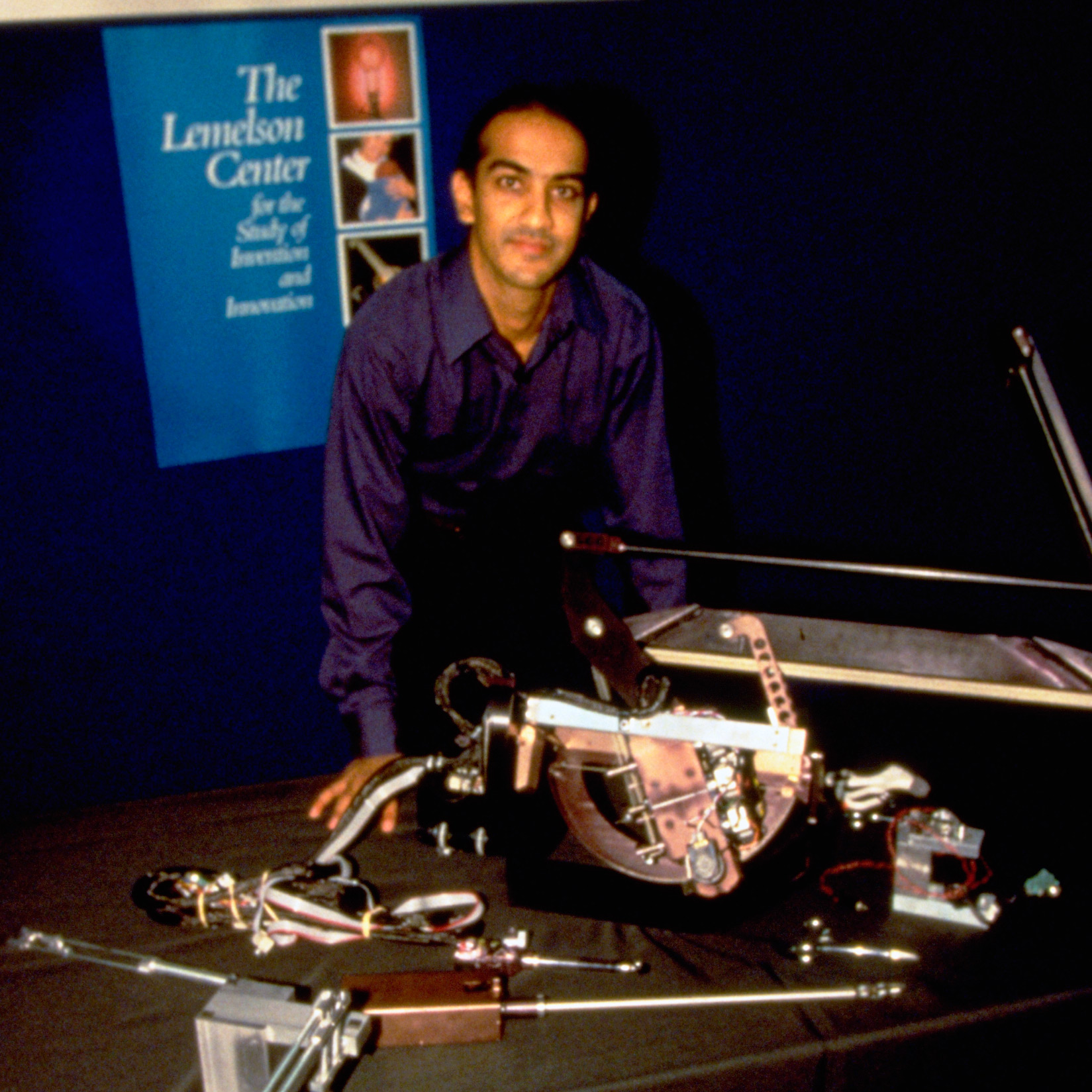 Image of Akhil Madhani with some of his robot inventions