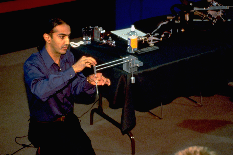 Image of Akhil Madhani demonstrating how robot arms work
