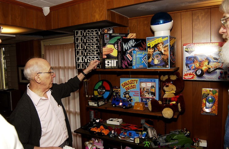 Ralph Baer pointing towards shelves holding game and toys he invented