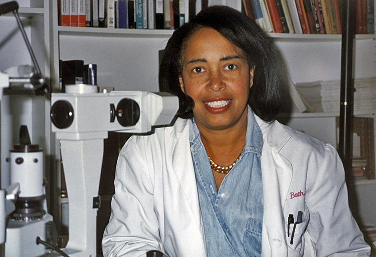 Dr. Bath in lab coat with microscope