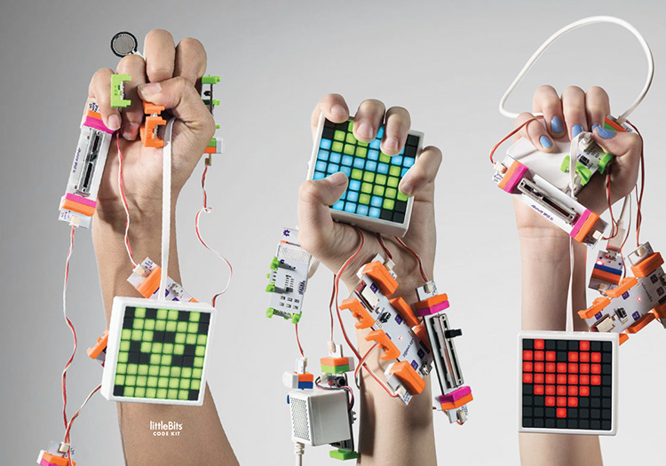 Three hands holding up connected littleBits