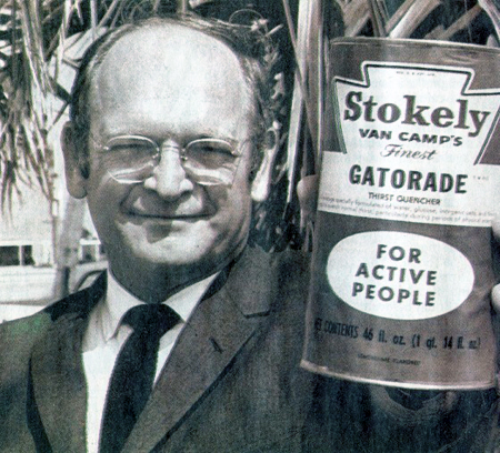 """Black-and-white head-and-shoulders photo of Robert Cade, wearing a jacket and tie. He holds a large can up to the camera. The can is labeled, """"Stokely Van Camp's Finest Gatorade for Active People."""""""