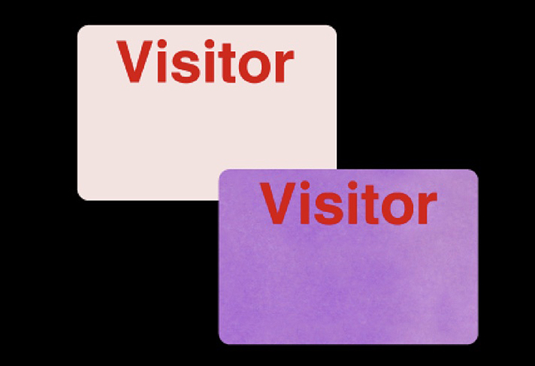 "Two badges reading ""Visitor,"" one with white background and the other with a purple background"