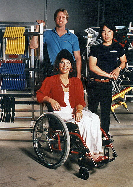 Hamilton in wheelchair with two men standing behind her