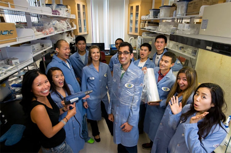 Khine with a group of students in blue lab coats pretending to shrink wrap one student