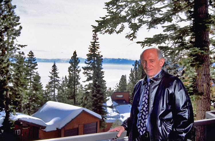 Jerome Lemelson standing on a deck overlooking snow-covered roofs and Lake Tahoe. He is smiling at the photographer.