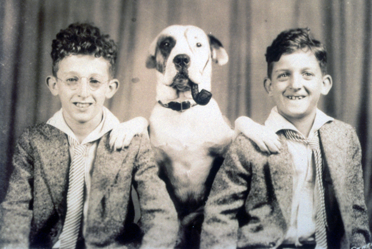 Jerome Lemelson as a child, posing with his brother Howard. The family dog is between the boys. The dog sits with his front paws on either boy's shoulder and has a pipe in its mouth. Its face has been painted to look like Petey, the dog in the Little Rascals Our Gang comedies.