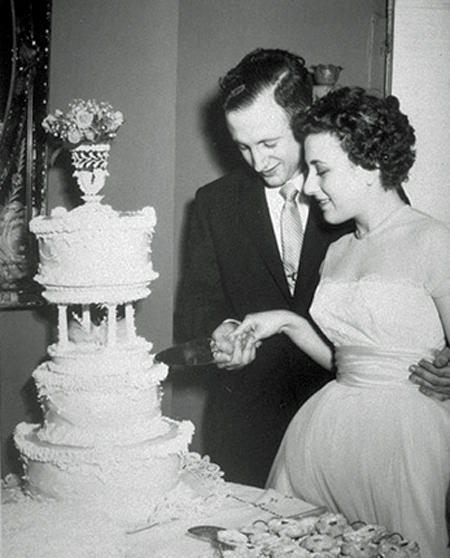Jerome and Dorothy Lemelson at their wedding. They jointly hold the knife and are beginning to cut the wedding cake. Jerry has his arm around Dorothy's waist.