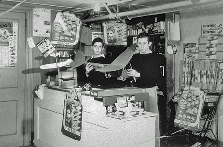 Howard and Jerome Lemelson stand behind the counter in a model airplane shop. They are holding a large model airplane.
