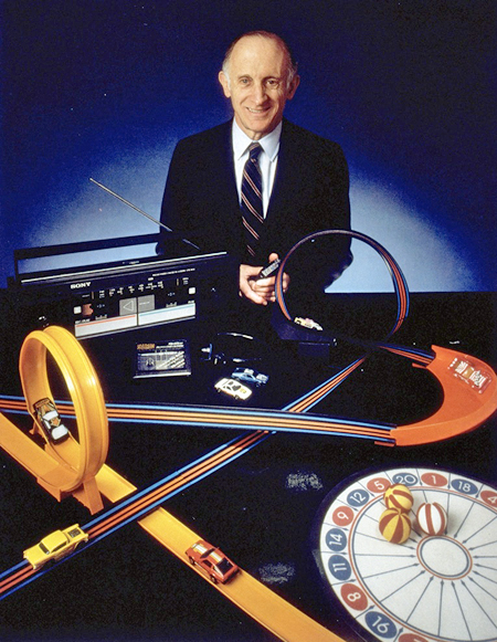 Jerome Lemelson, smiling at the camera, overlooks a display of some of the products he invented, including a Velcro target game, flexible toy car race track, and a Sony dual cassette recorder-player.