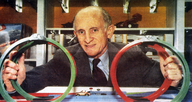 Jerome Lemelson smiling at the photographer. He is seated at a table and holds a loop of flexible track for toy cars in each hand.