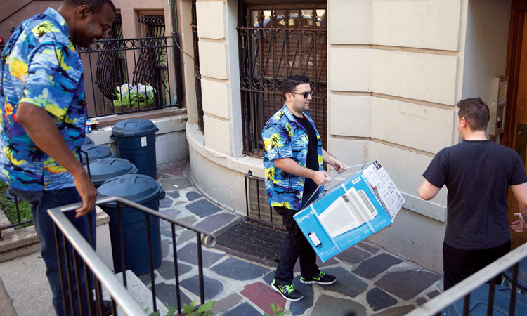 Inventor Garthen Leslie at top of stairs to a basement apartment, with Quirky founder Ben Kaufman at bottom, carrying an Aros air conditioner to be delivered. Garthen and Kaufman wear Hawaiian shirts. A third man is at the apartment building door.