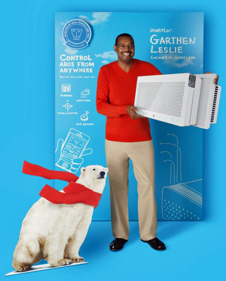Advertising image showing inventor Garthen Leslie holding the Aros air conditioner that he invented. He stands against a backdrop of blueprint-type sketches for the air conditioner. A cut-out of a polar bear wearing a red scarf is at his feet.
