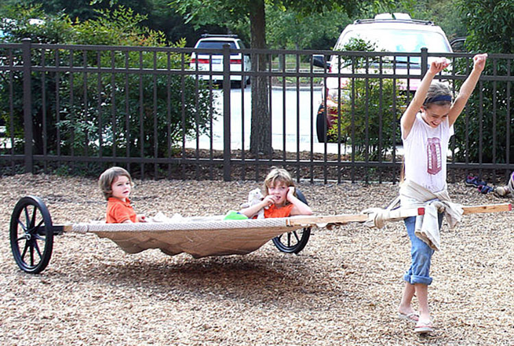 Two small children riding in the travois while a third child pulls it.
