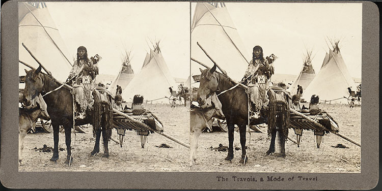 Historic photo of Native Americans with traditional travois sled