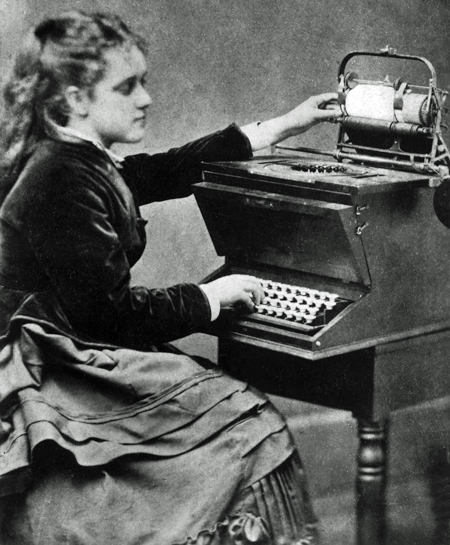 Lillian Sholes seated at a Remington Model 1 typewriter, about 1874