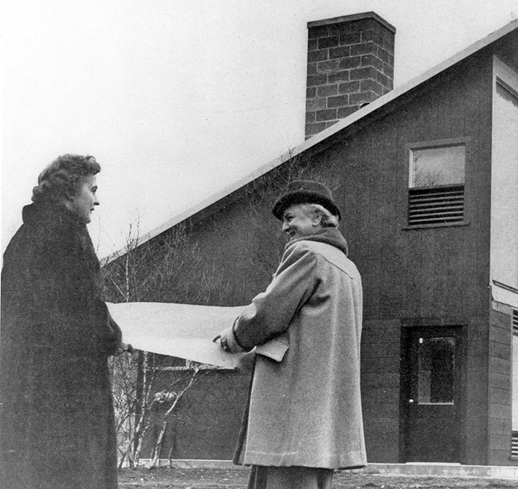 Telkes and architect Raymond looking at plans outside solar house
