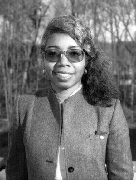 Informal portrait photo of Valerie L. Thomas, 1995. She is standing outside, with trees in the background. She is wearing tinted glasses and an unbuttoned jacket.