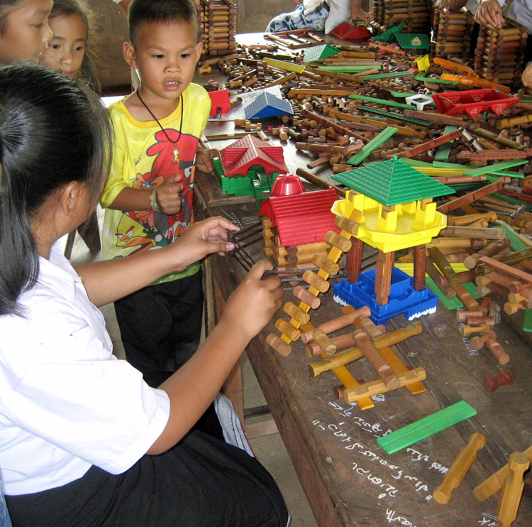 4 young children at a table covered with modern day Lincoln Logs. One girl is building a house on stilts with a ladder entrance and another traditional building surrounded by a fence, while the other children look on.