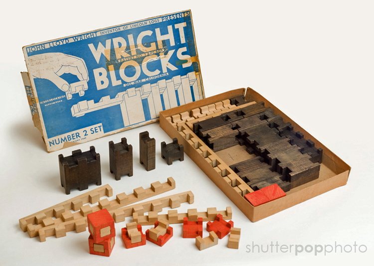 "An open box of Wright Blocks. The blue-and-white box cover reads ""John Lloyd Wright, Inventor of Lincoln Logs, Presents Wright Blocks, Number 2 Set. Some brown, tan, and red notched blocks are still in the box while others are arranged on the table."