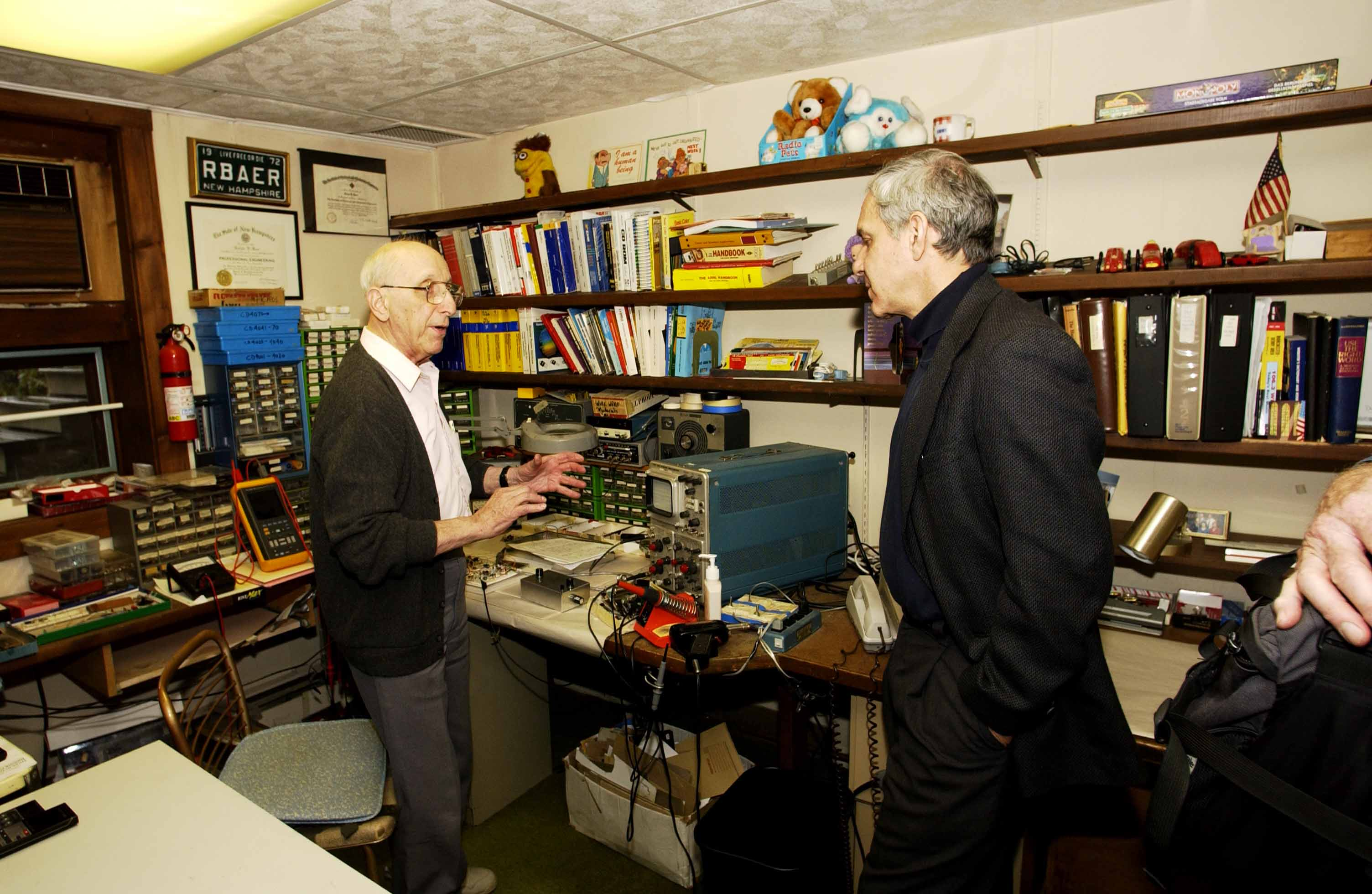 Video game inventor Ralph Baer shows Lemelson Center Director Art Molella his basement workshop.